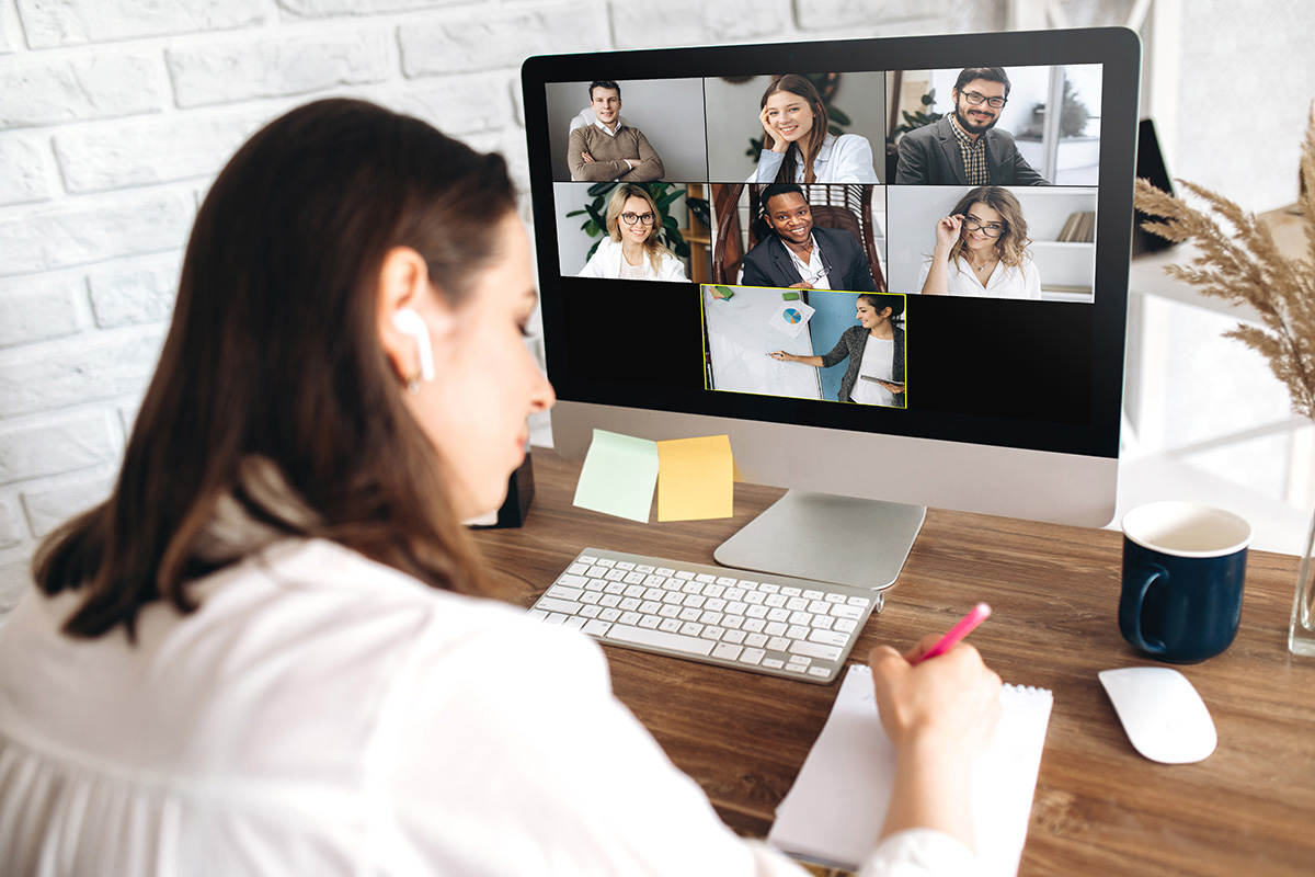 A woman taking notes during a virtual meeting