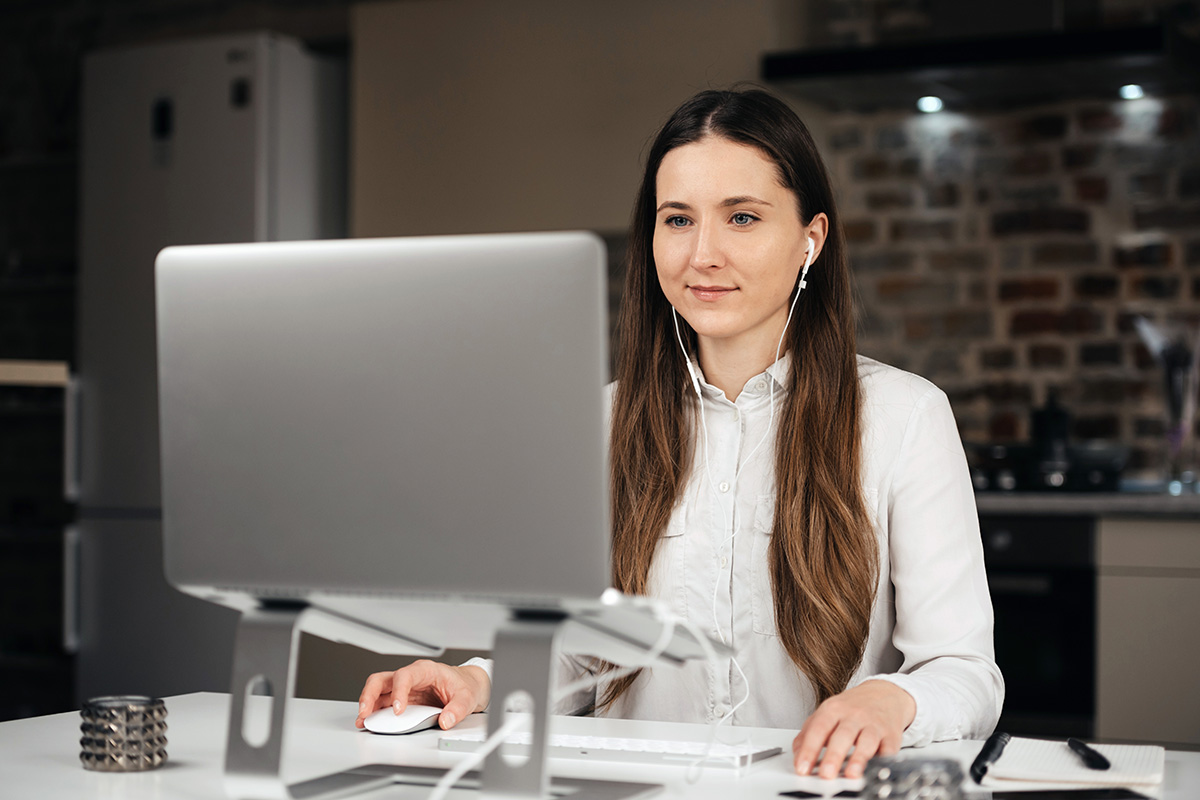 Woman looking at her laptop with earphones on