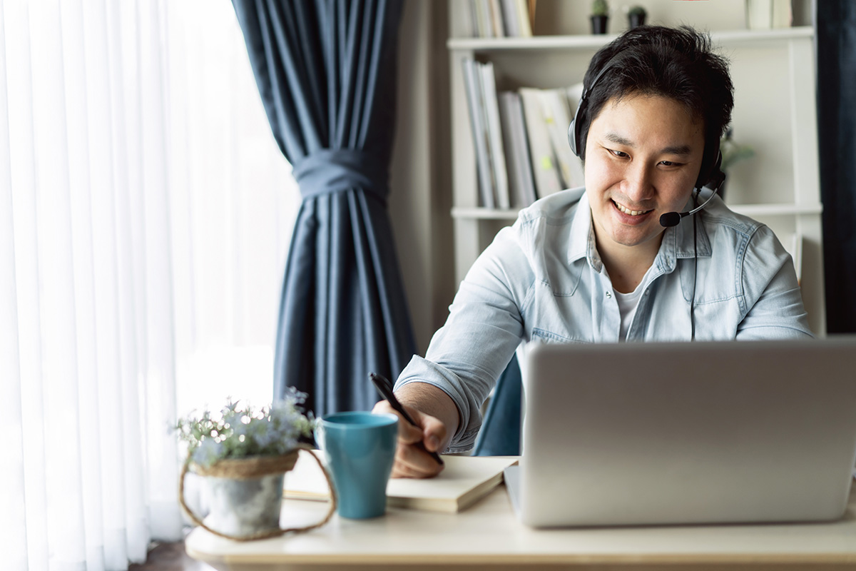 A man smiling and taking notes while working on his laptop