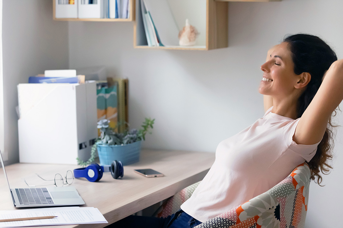 A woman leaning back on her chair and resting