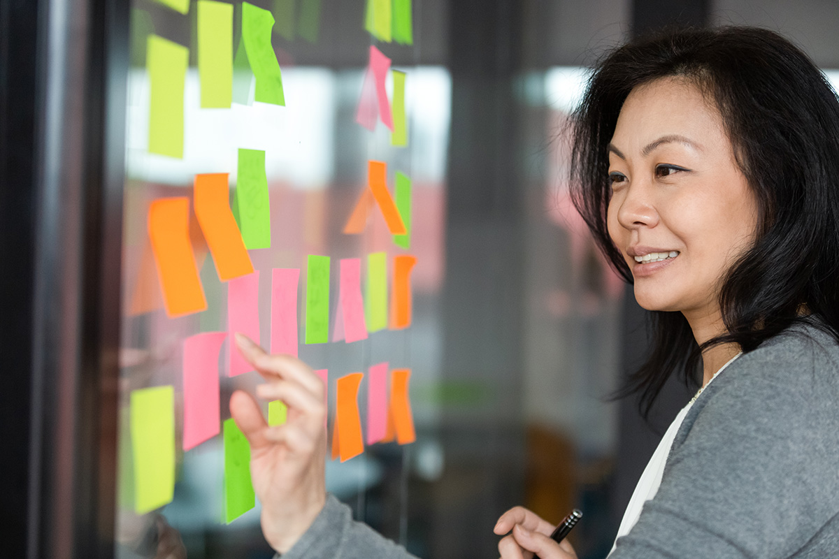 How to Be Selfish With Your Time, Without Being a Jerk: Woman looking at post-it notes on a glass wall