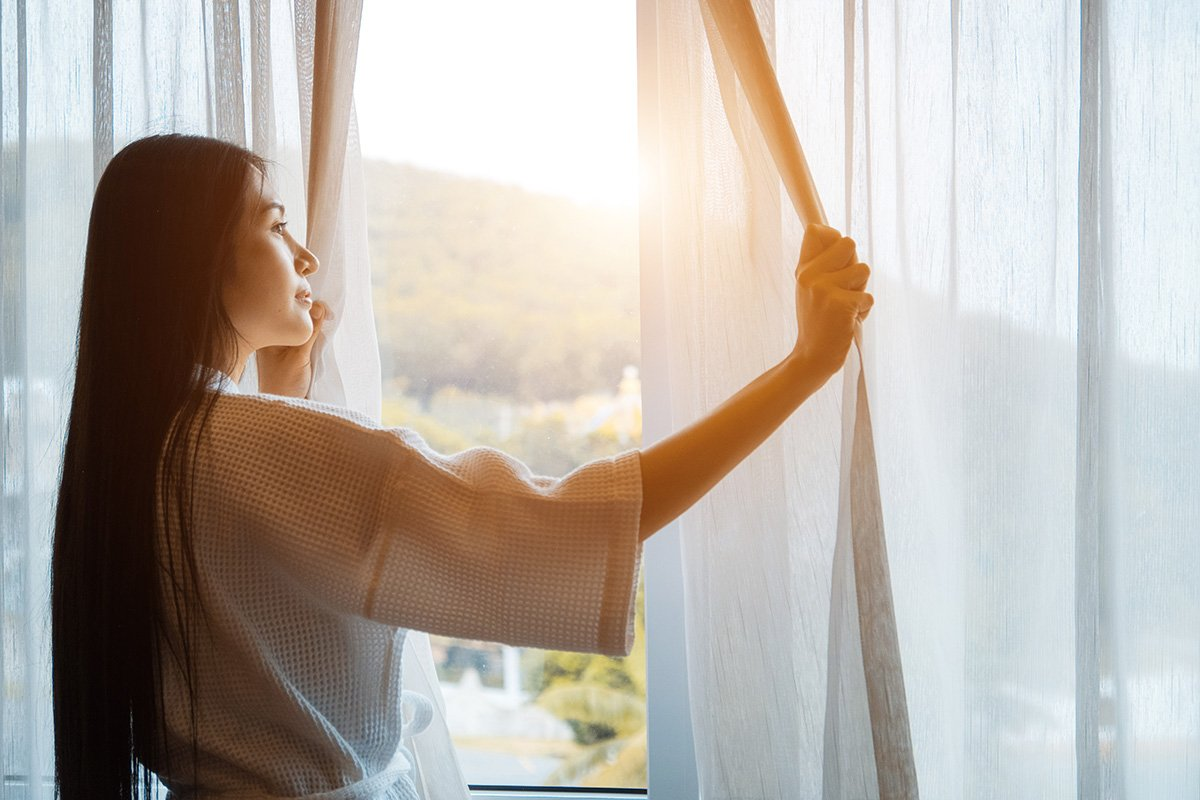 Woman looking outside her window in the morning