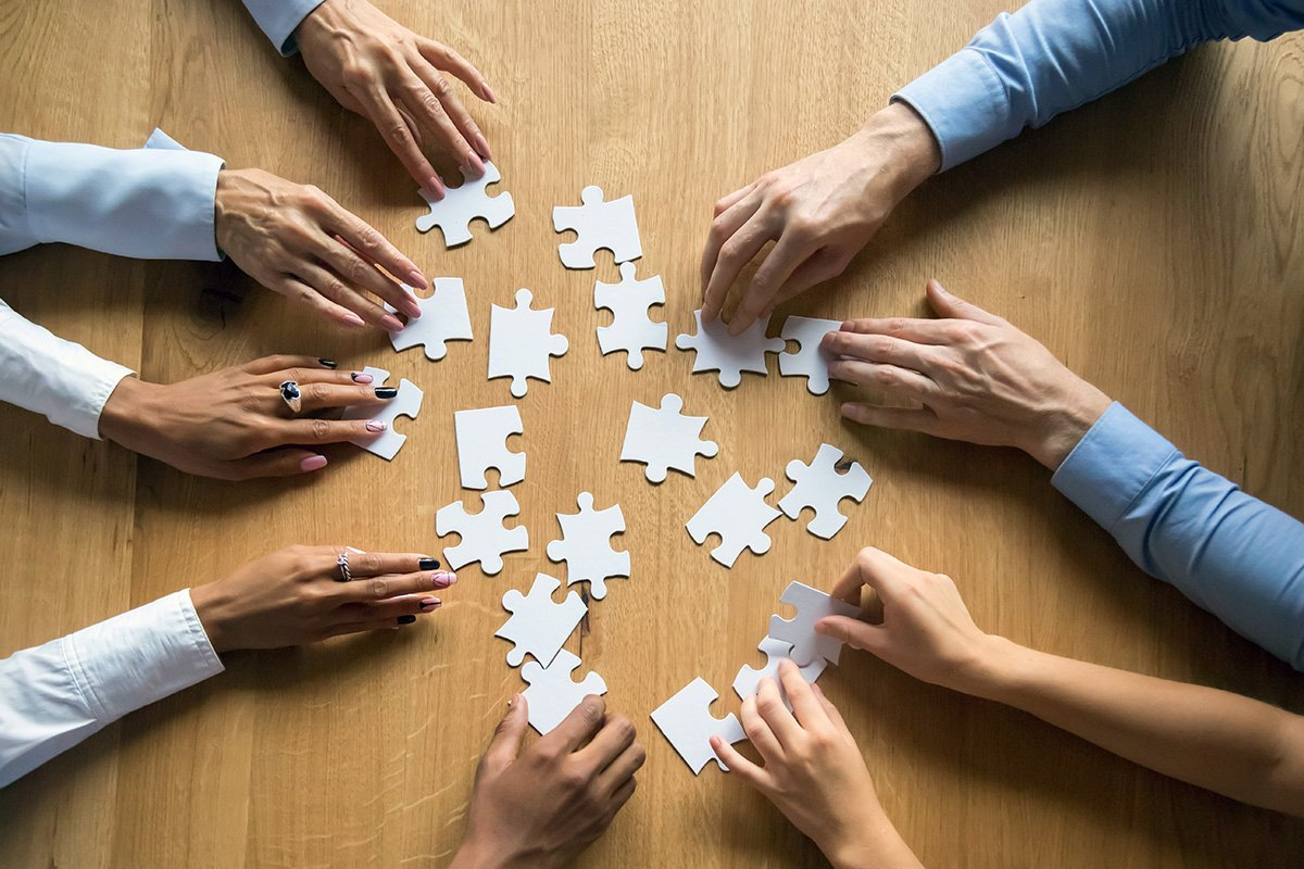 Several hands piecing together a puzzle