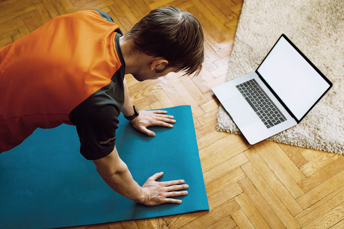 A man doing push-ups in front of his laptop