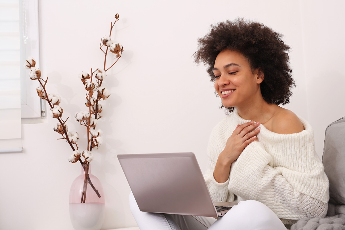 A woman looking at her laptop with a smile on her face