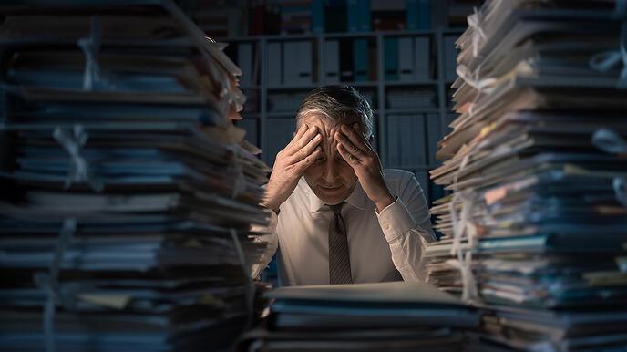 Overworked Employee with his hands on his head, surrounded by mountains of paperwork on his desk.