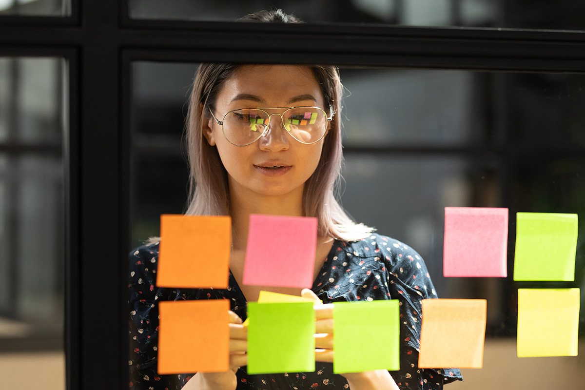Woman looking at a glass wall with post-it notes stuck on it